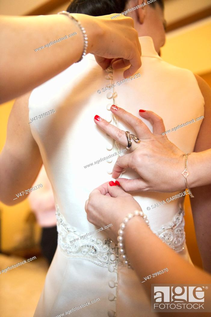 Stock Photo: Close-up of the hands of friends and family helping to take the buttons of the suit to the bride.