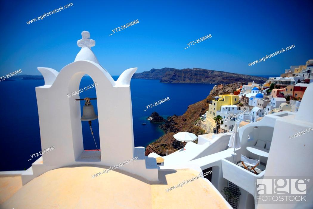 Stock Photo: Church bell and hillside buildings in Oia, Santorini, Greek Islands, Greece.