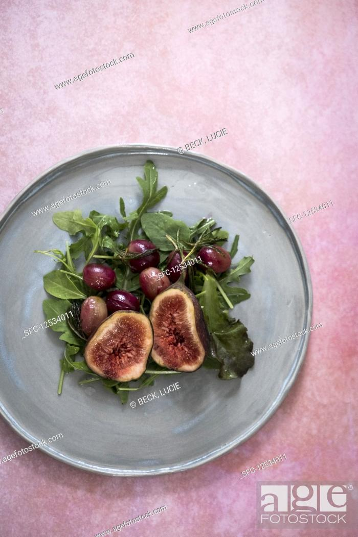 Imagen: A salad with figs, garpes and lettuce on a grey plate on a pink backdrop.
