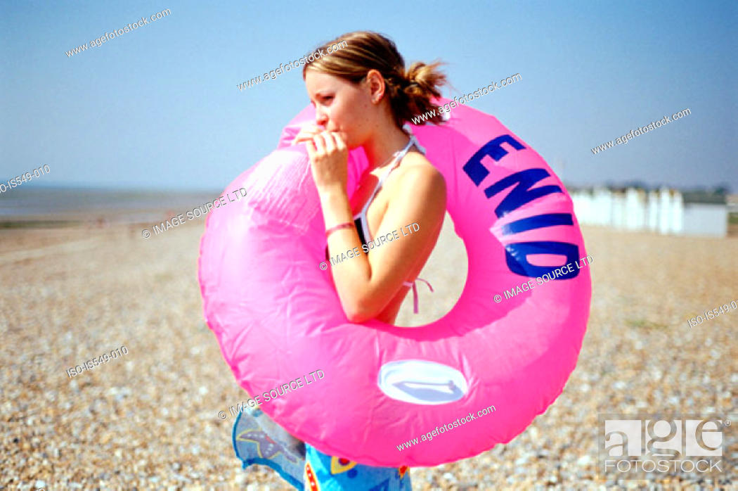 Stock Photo: Girl on the beach with inflatable lifebelt.