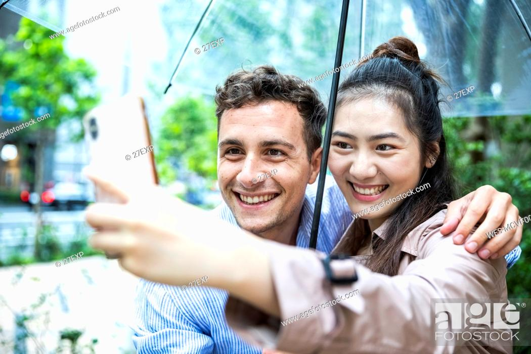 Stock Photo: Happy couple with umbrella taking a selfie in Ginza, Tokyo, Japan.