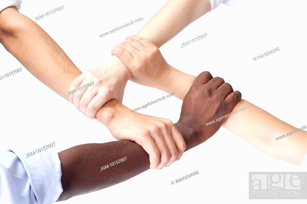Stock Photo: Close-up of different ethnic people's arms holding one another.