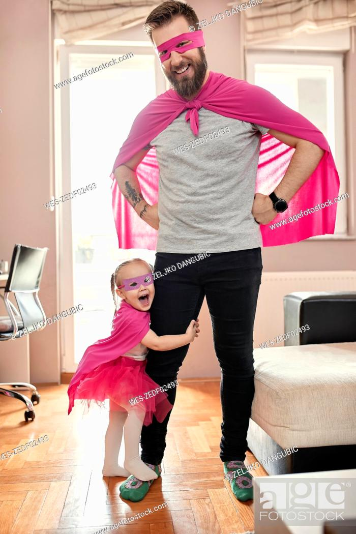 Imagen: Father and daughter playing super hero and superwoman.