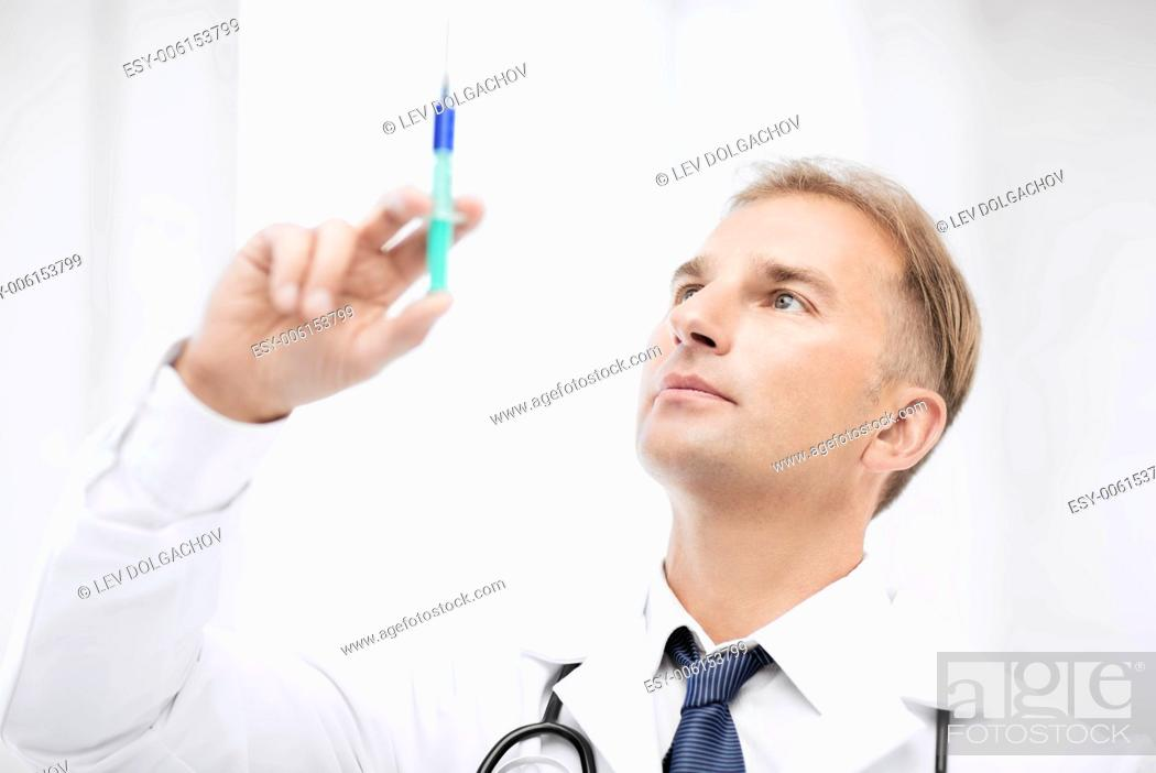 Stock Photo: healthcare and medical concept - male doctor holding syringe with injection.