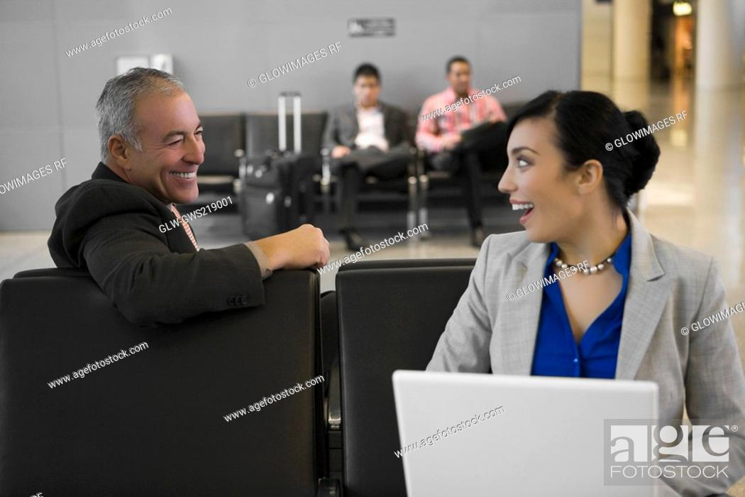 Stock Photo: Side profile of a businessman with a businesswoman looking at each other and smiling at an airport.