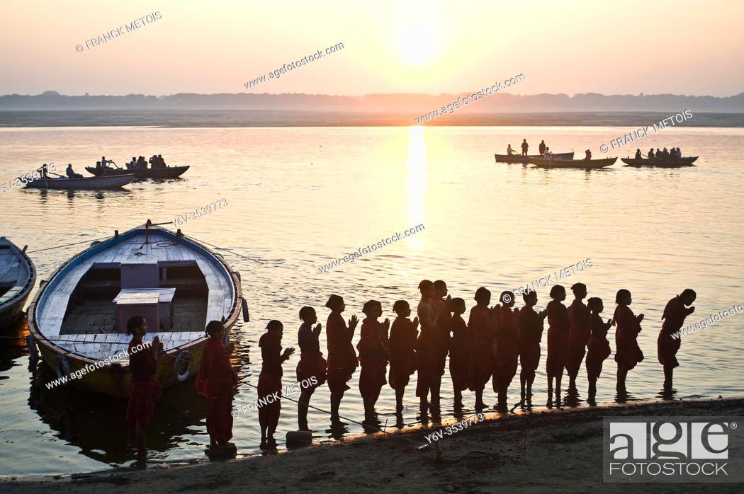 "Stock Photo: Schoolboys from a """"gurukul"""" ( hindu school) are praying the rising sun ( the sun is the hindu god Surya) ( Ganges river in Varanasi, India)."