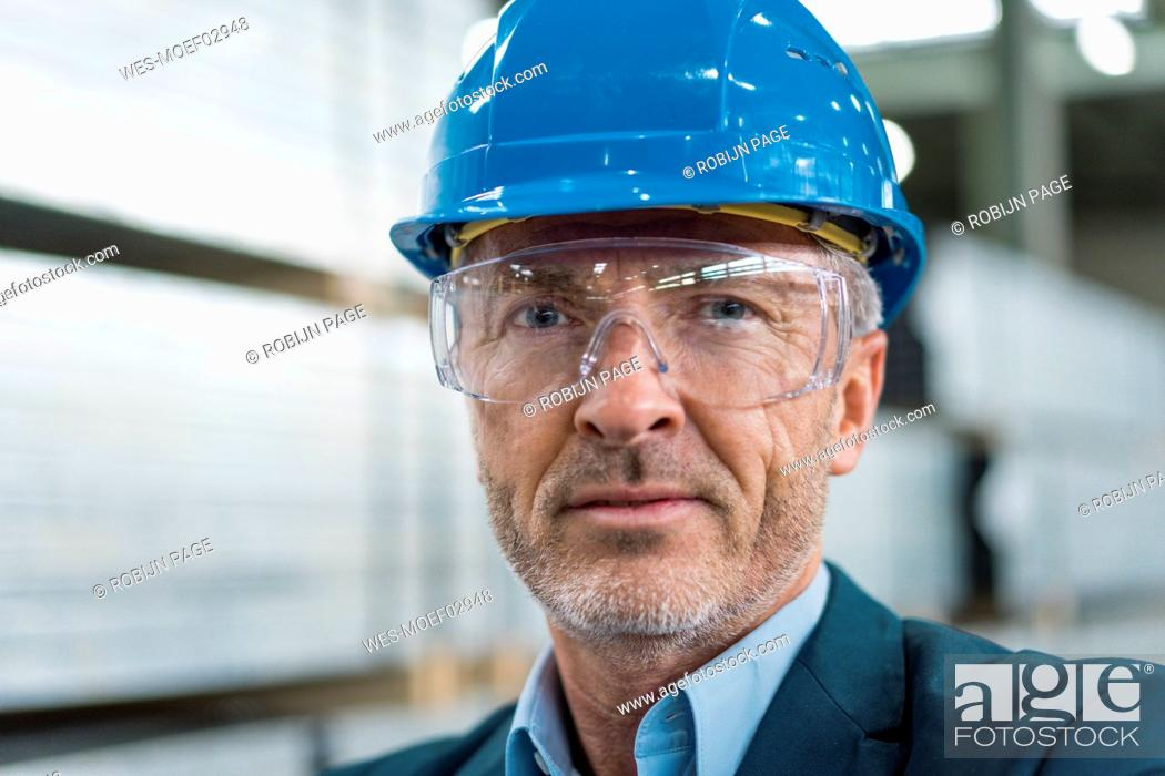 Stock Photo: Portrait of mature businessman wearing hard hat and safety goggles in a factory.