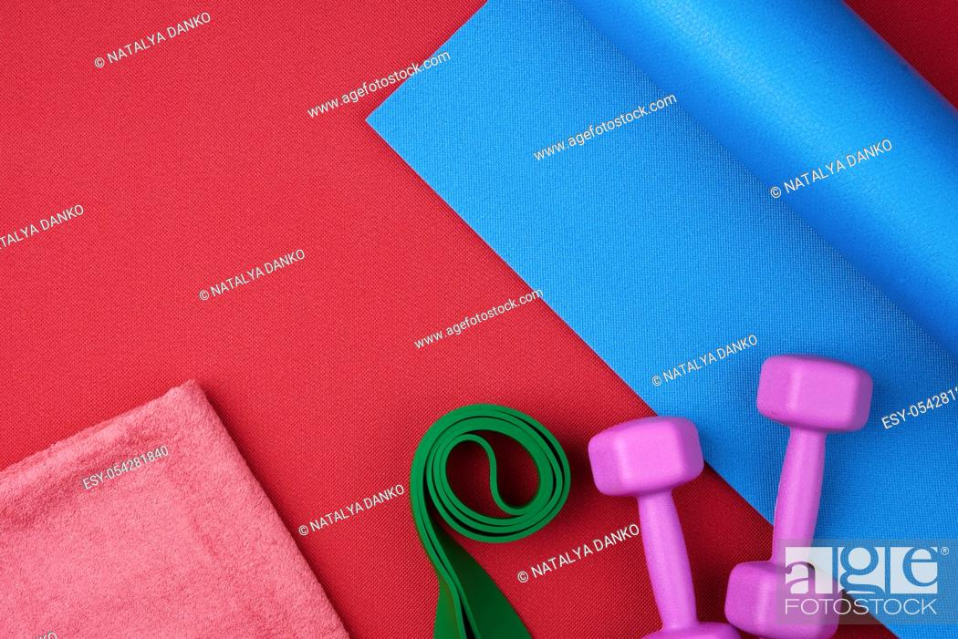 Stock Photo: pair of purple plastic dumbbells, green elastic and pink terry towel on a blue neoprene mat, top view, training equipment.