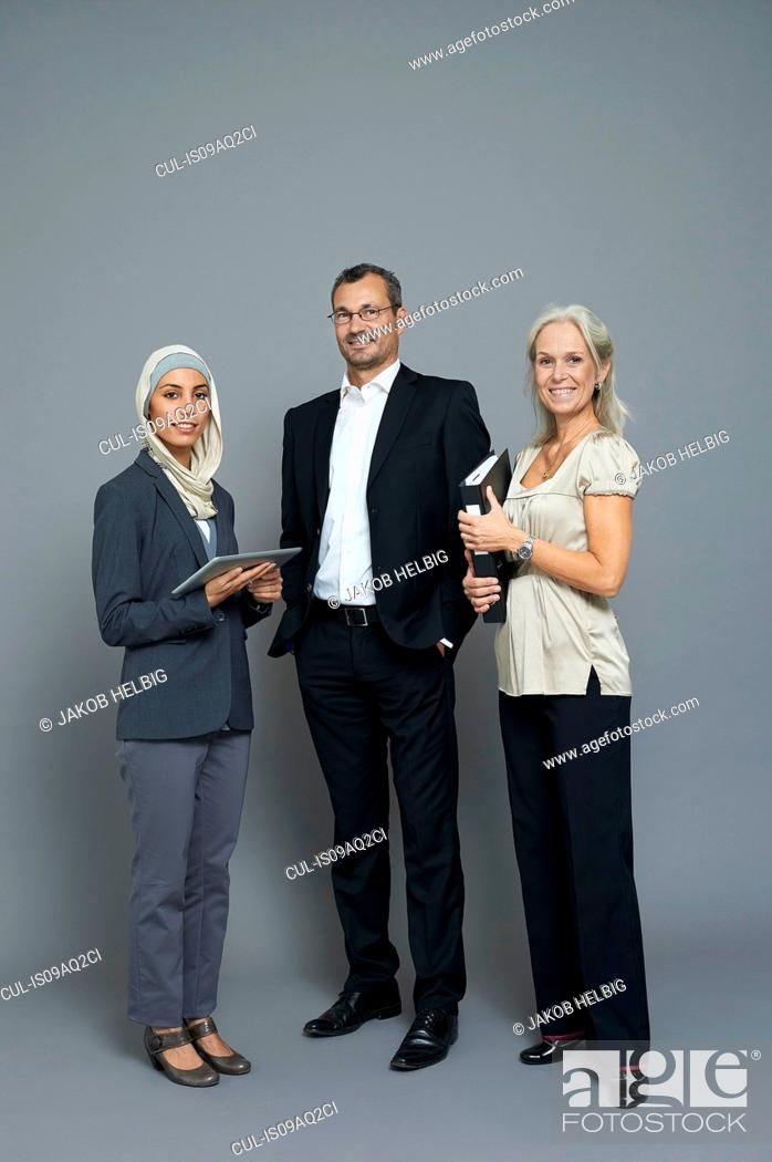 Stock Photo: Studio portrait of two businesswomen and businessman.