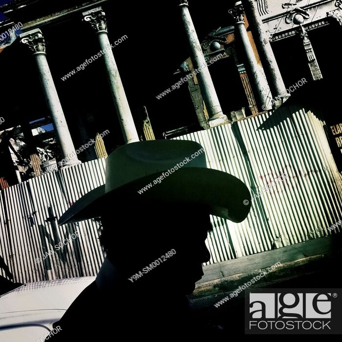 Stock Photo: A Salvadorean man, wearing a cowboy hat, walks along a ruined colonial building on the street of San Salvador, 20 December 2013.