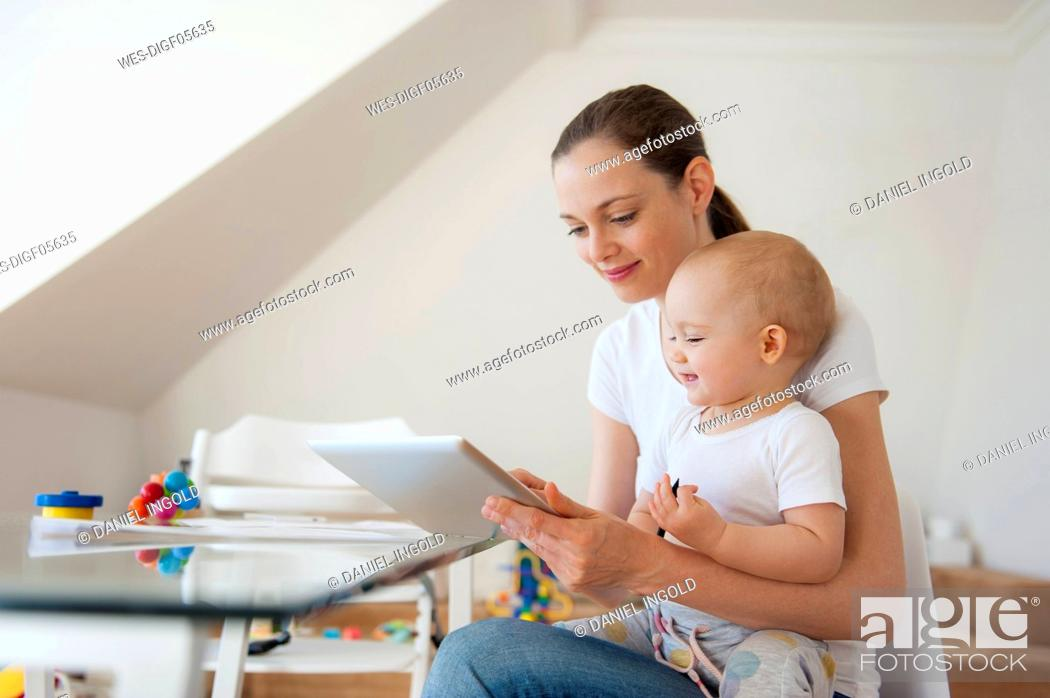 Stock Photo: Mother and little daughter using tablet together at home.