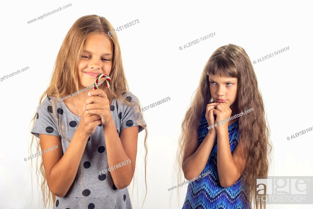Stock Photo: One girl has a lollipop in her hands, the other behind her looks at the girl reproachfully.