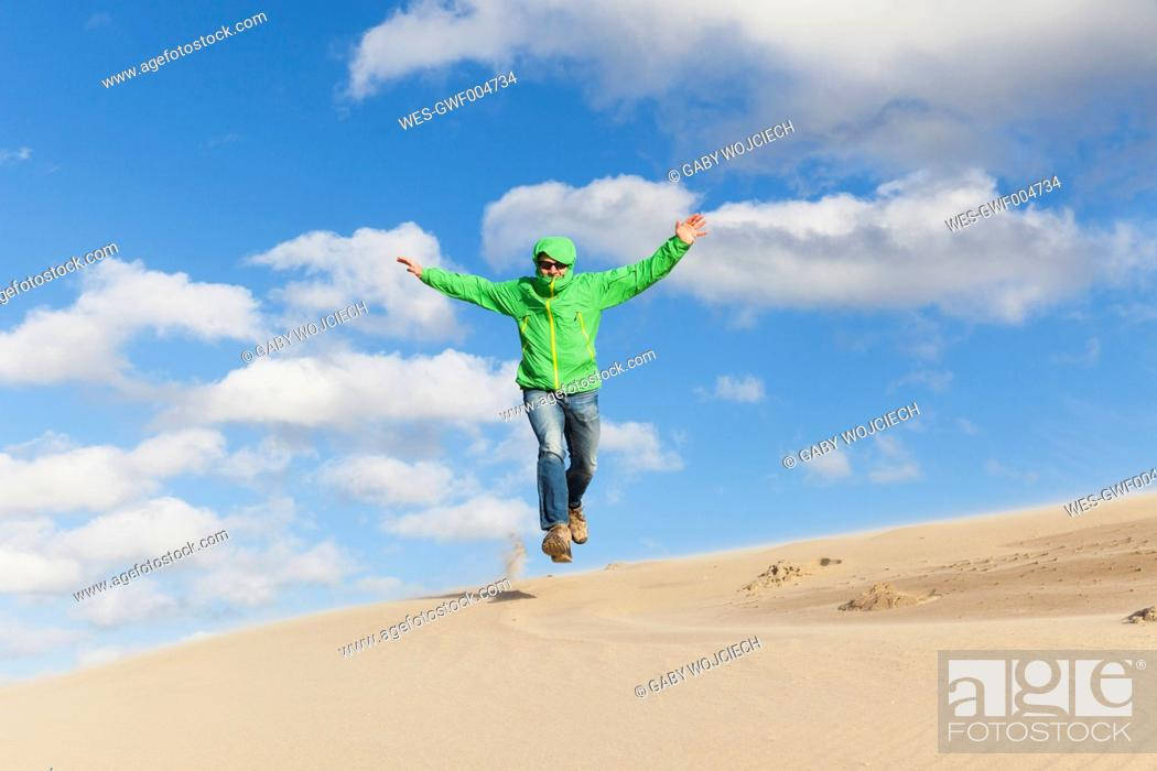 Photo de stock: Enthusiastic mature man jumping over sand dune.