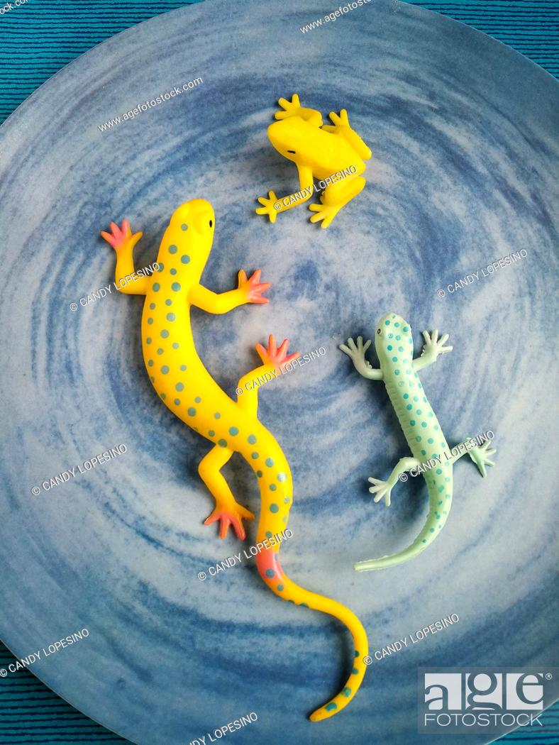 Stock Photo: Colorful plastic reptiles an amphibian on blue background.