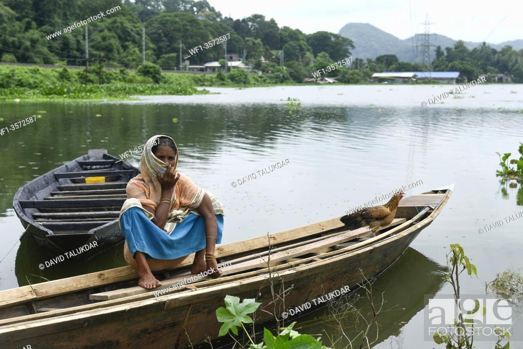 Stock Photo: A woman siting on a boat in a flood effected village in Kamrup district of Assam, Monday, July 13, 2020.