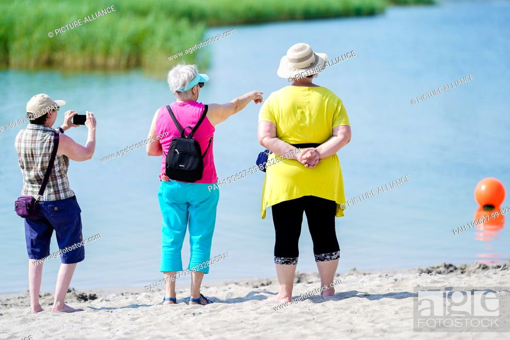 Stock Photo: 27 June 2019, Baden-Wuerttemberg, Heilbronn: Visitors stand on the grounds of the Federal Garden Show at the sandy beach of Karlssee.