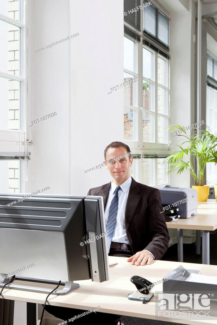 Stock Photo: A businessman sitting at a desk in his office.