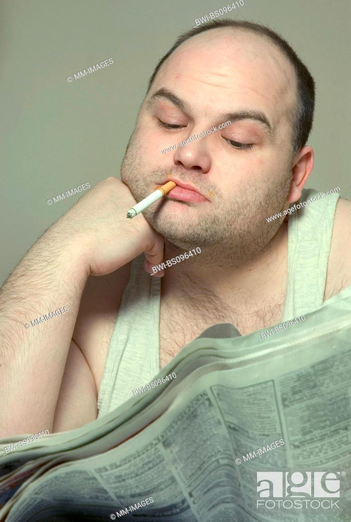 Stock Photo: thick man with cigarette and newspaper, Germany.
