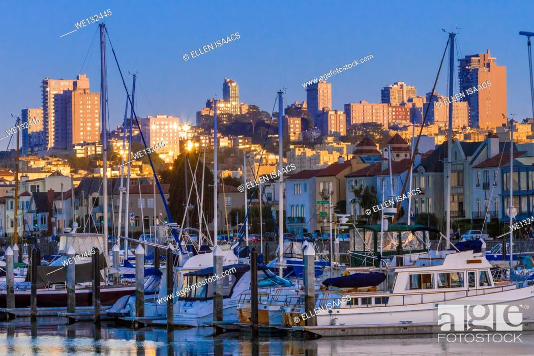 Stock Photo: Boats docked in harbor in front of marina district houses and San Francisco skyline at twilight.