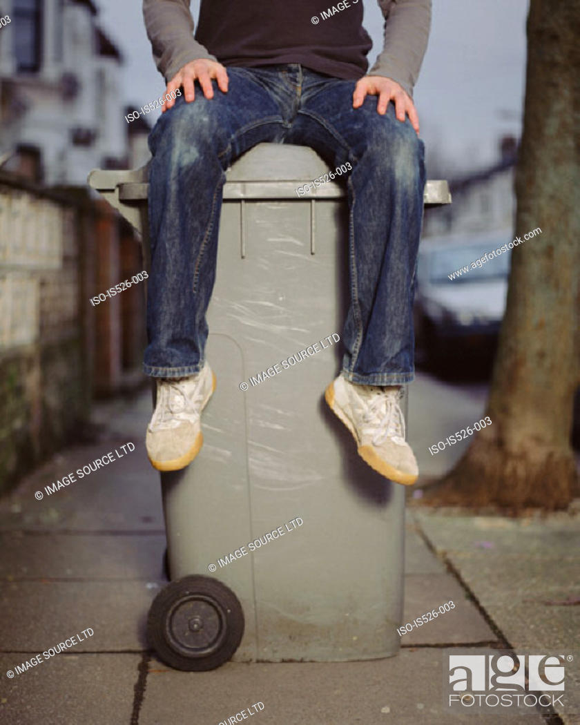 Stock Photo: A young man sitting on a wheelie bin.