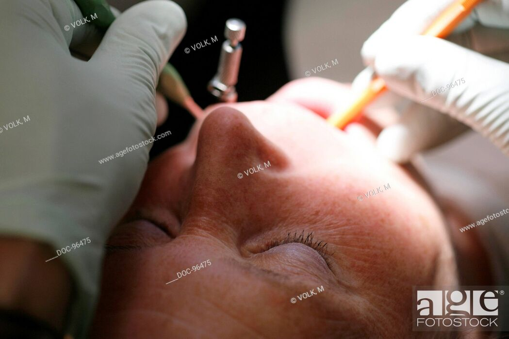 Stock Photo: dental practice : a male or female dentist treats a female patient with a probe and an inspection mirror.