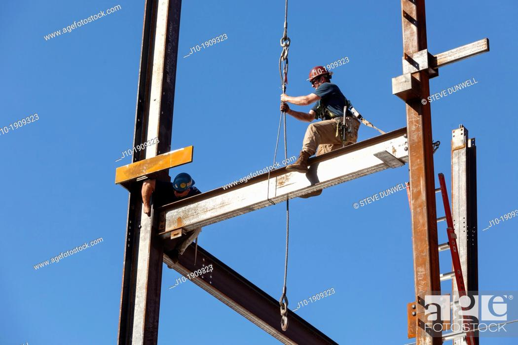 Stock Photo: Steel workers assemble building framework girders, Boston, MA.