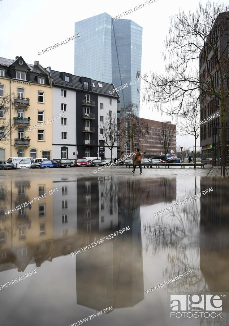 Stock Photo: The European Central Bank (ECB) headquarters rising into the sky and being reflected by a puddle in a square in the Ostend district of Frankfurt am Main.