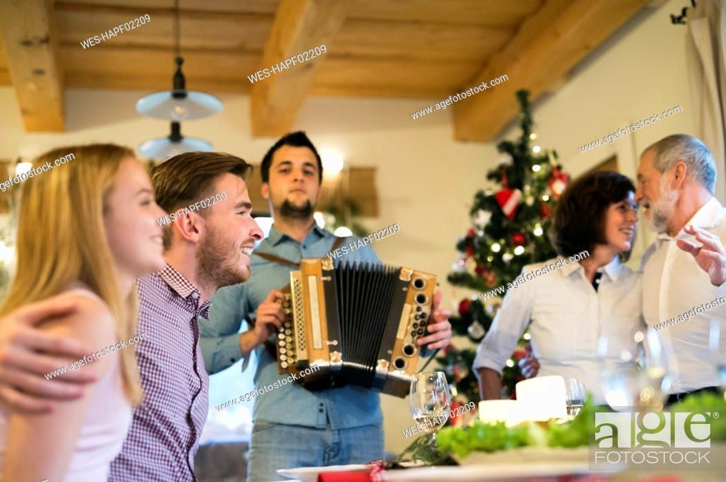 Stock Photo: Young man playing accordion for family at Christmas.