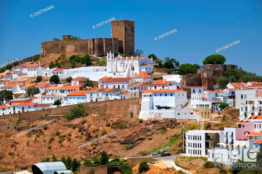 Stock Photo: The mediaeval castle on the top of the hill surrounded by residential Alentejo country-style houses inside the old city walls of Mertola.