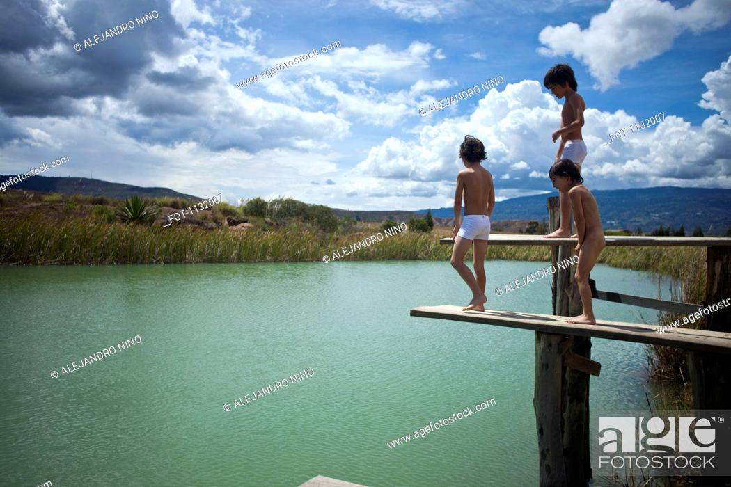Stock Photo: Twin brothers and their friend preparing to jump into a lake.