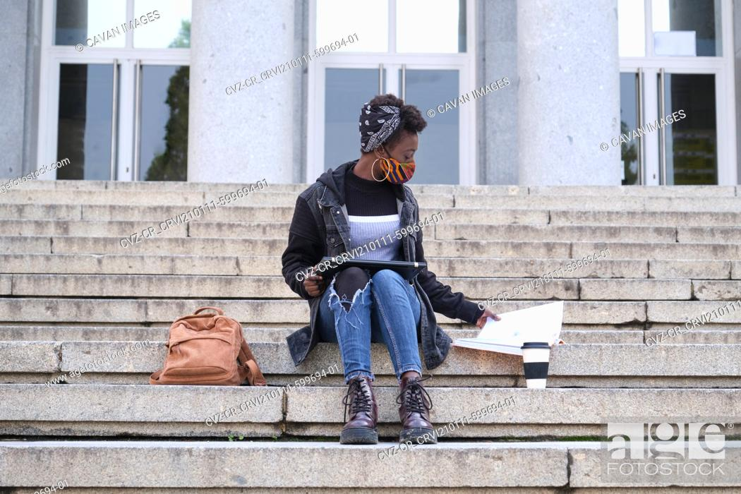 Stock Photo: University female african student wearing protective face mask studying sitting on stairs outside on campus. New normal in college.