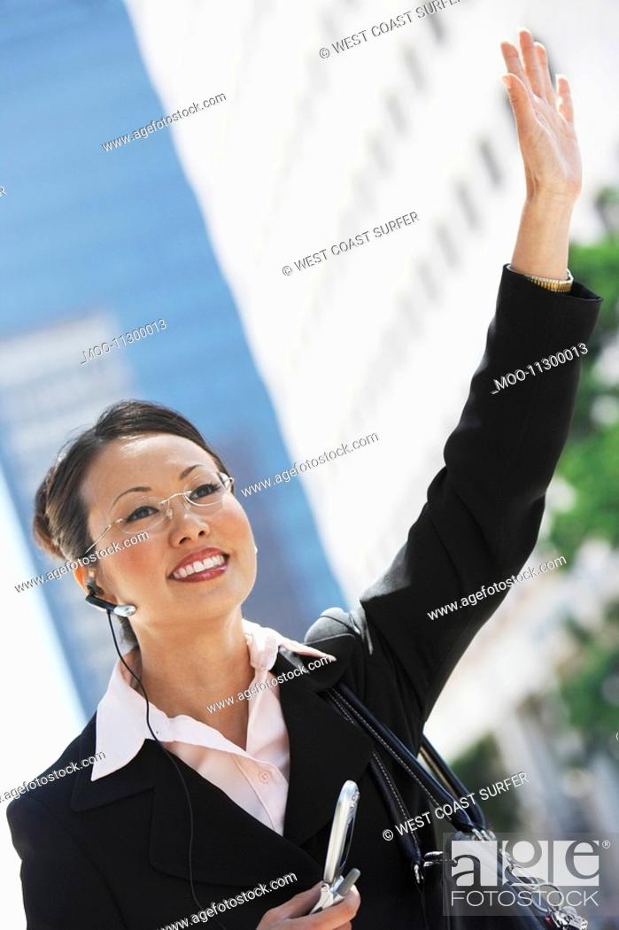 Stock Photo: Businesswoman Hailing Cab using Cell Phone with hands free.