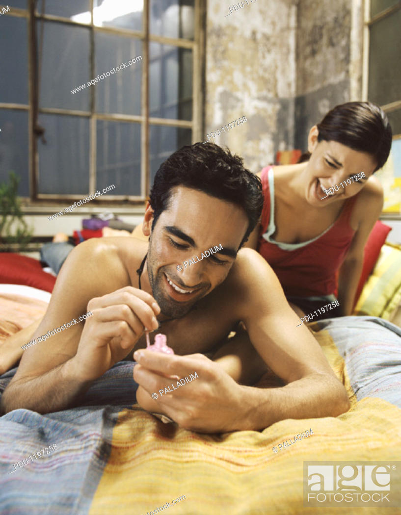 Stock Photo: Young Man Lies on a Bed, Painting His Girlfriend's Toenails.
