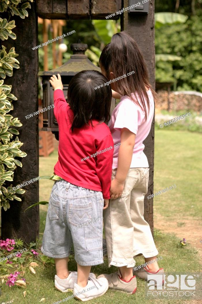 Stock Photo: Rear view of two children looking at a metallic structure.