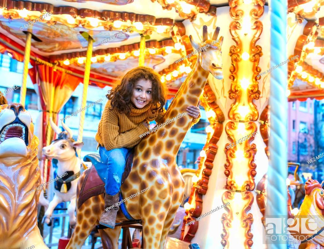 Imagen: Portrait of little girl sitting on giraffe of a carousel.