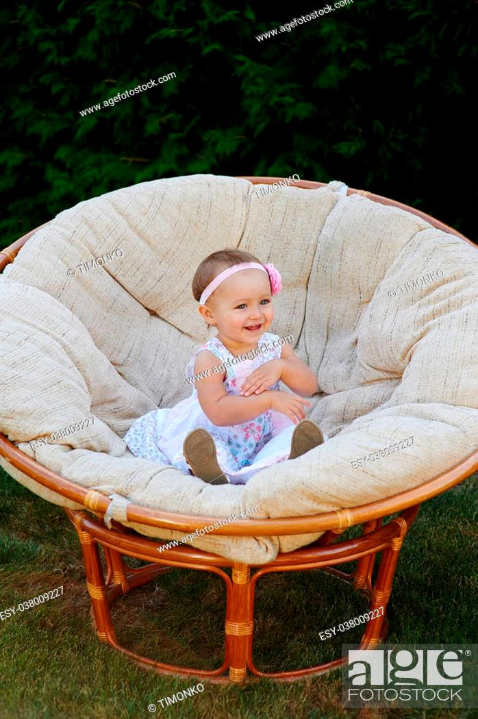 Stock Photo: Little baby girl poses on a white chair. She is smiling happily.