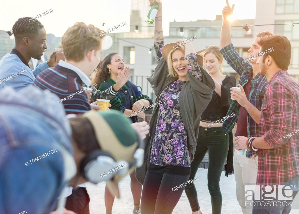 Imagen: Playful young adult friends dancing at rooftop party.