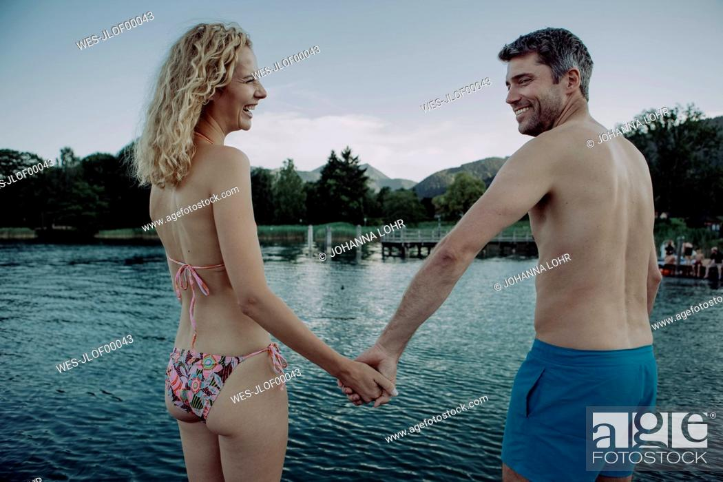 Stock Photo: Happy couple hand in hand at swimming lake.