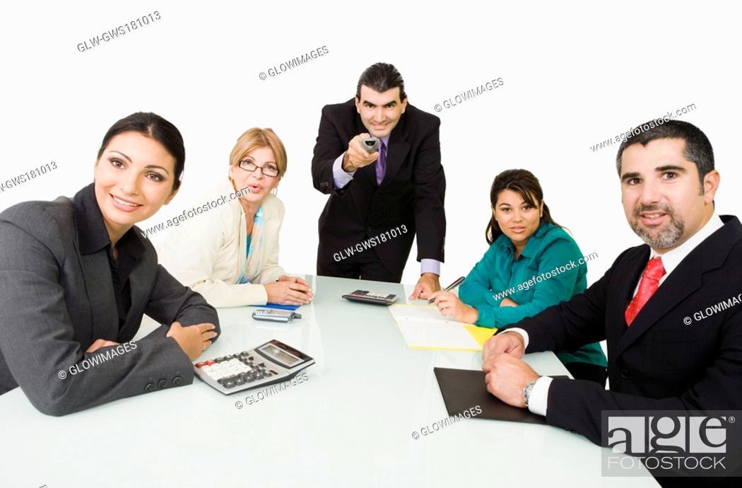 Stock Photo: Portrait of three businesswomen with two businessmen watching a presentation.