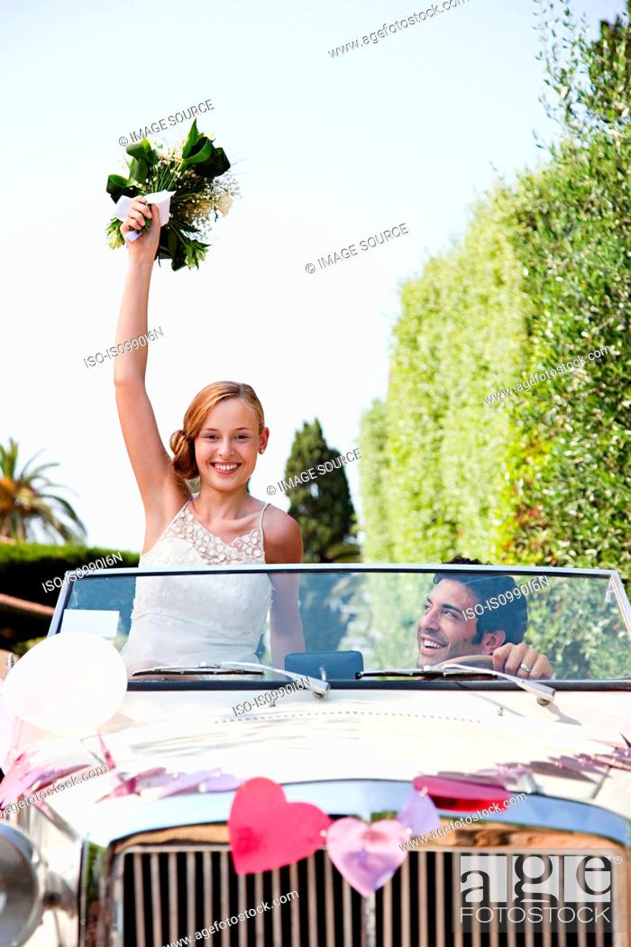 Stock Photo: Newlyweds in classic car, bride holding bouquet.