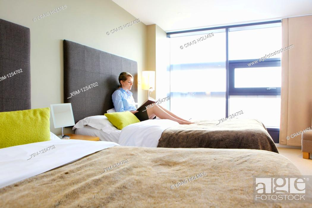 Stock Photo: Woman reading a book sitting on a bed in an apartment.