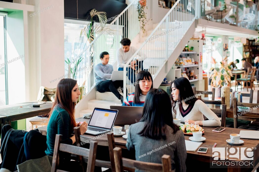Stock Photo: Young businesswomen remote working having meeting at cafe table.