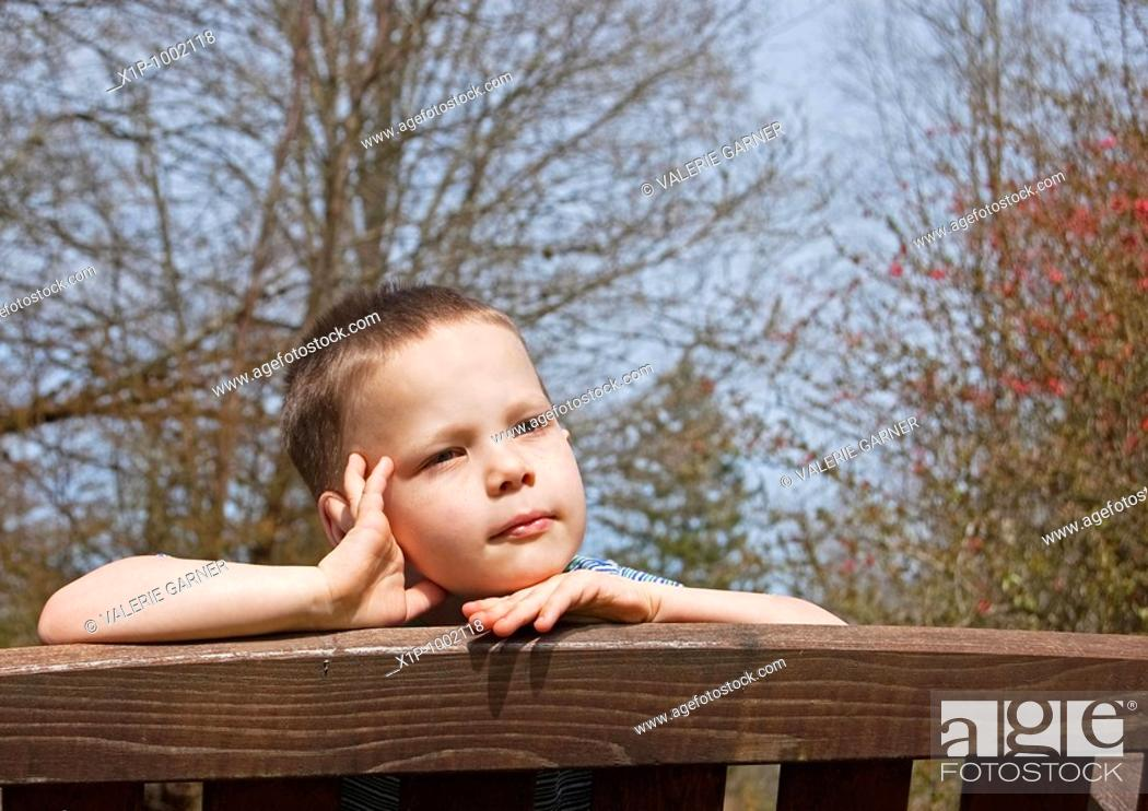 Stock Photo: This little boy has an expression as tho dreaming for summer with the bare branches of early spring in the background Background is intentionally blurred for.