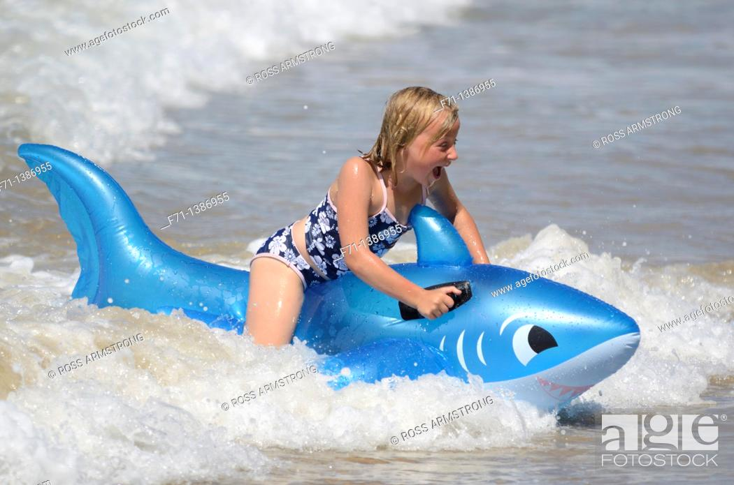Stock Photo: Six year old girl at the beach playing in the surf on inflatable shark Mimiwhangata Northland, New Zealand.