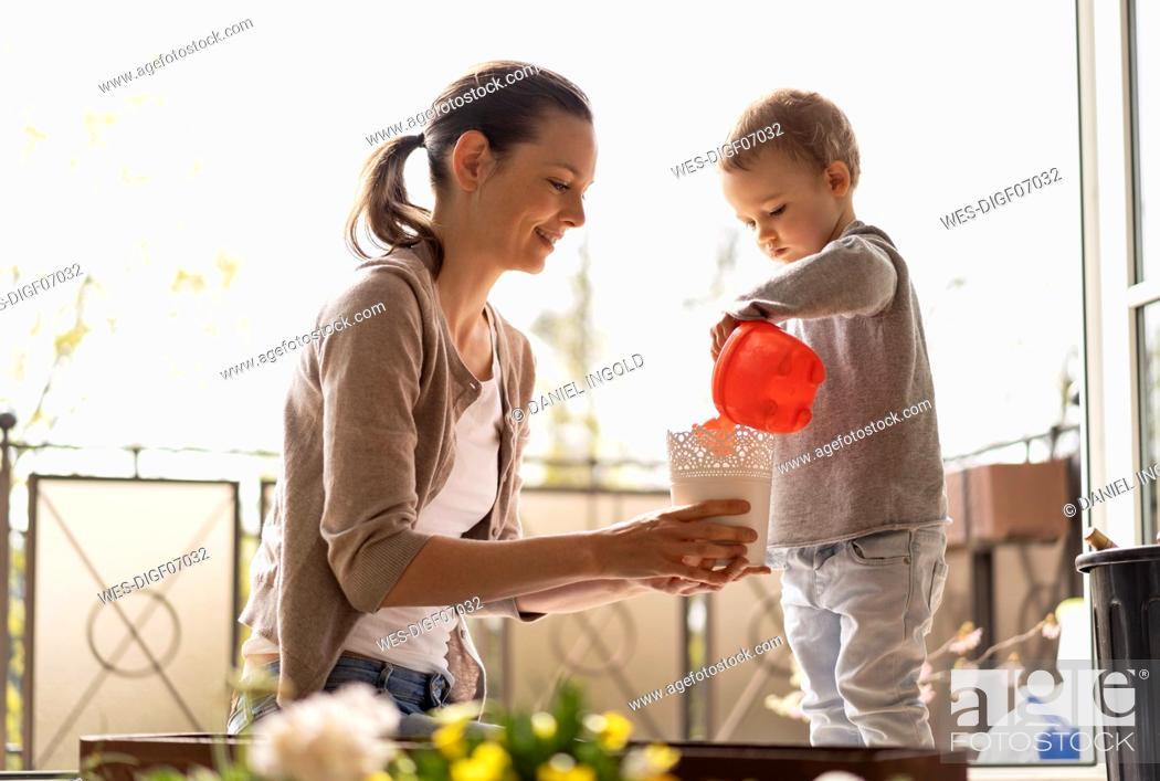 Stock Photo: Mother and daughter planting flowers together on balcony.