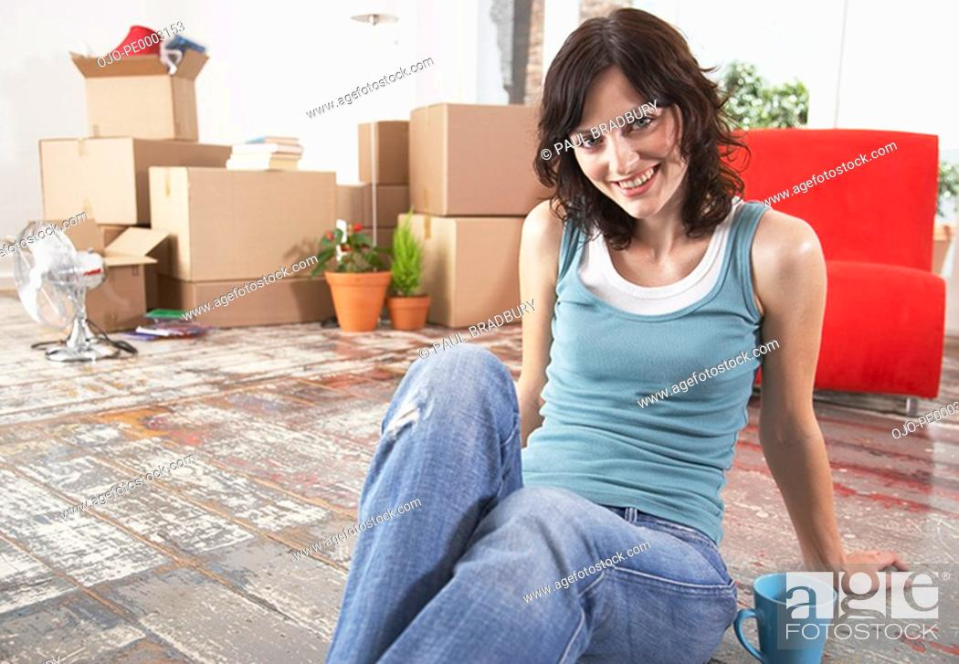 Stock Photo: Woman sitting on hardwood floor with mug and cardboard boxes smiling.