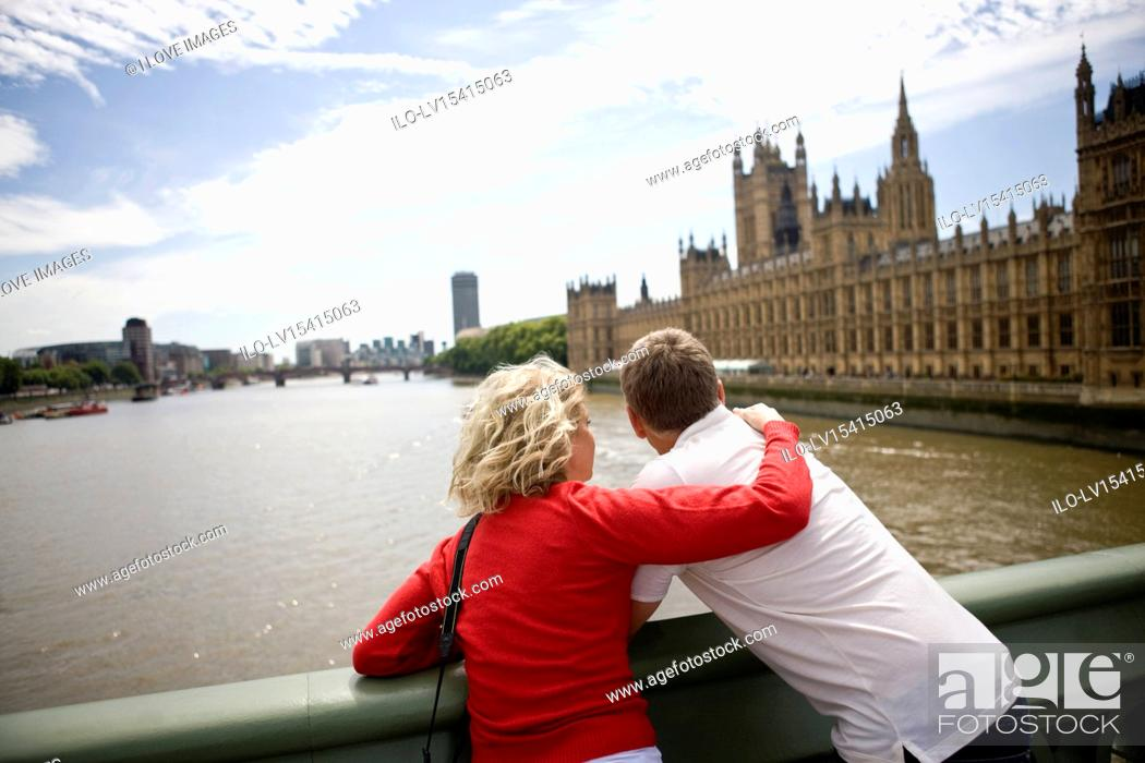 Stock Photo: A middle-aged couple standing near the Houses of Parliament, looking along the river Thames.