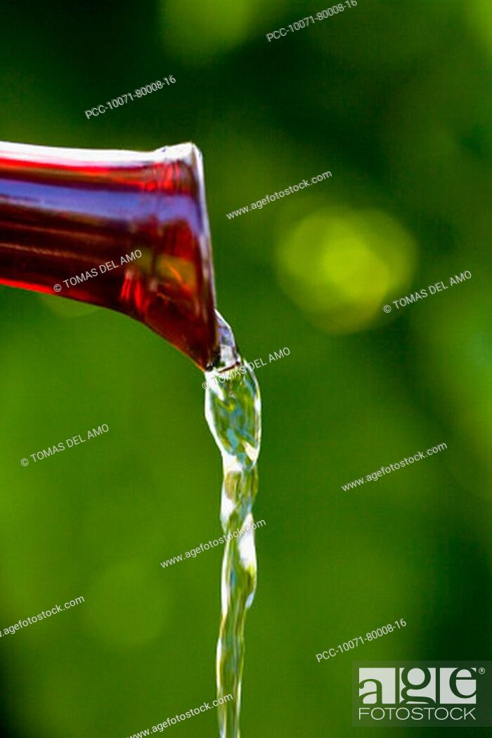 Stock Photo: Spa elements, red glass spout pouring water, gren blurred background.