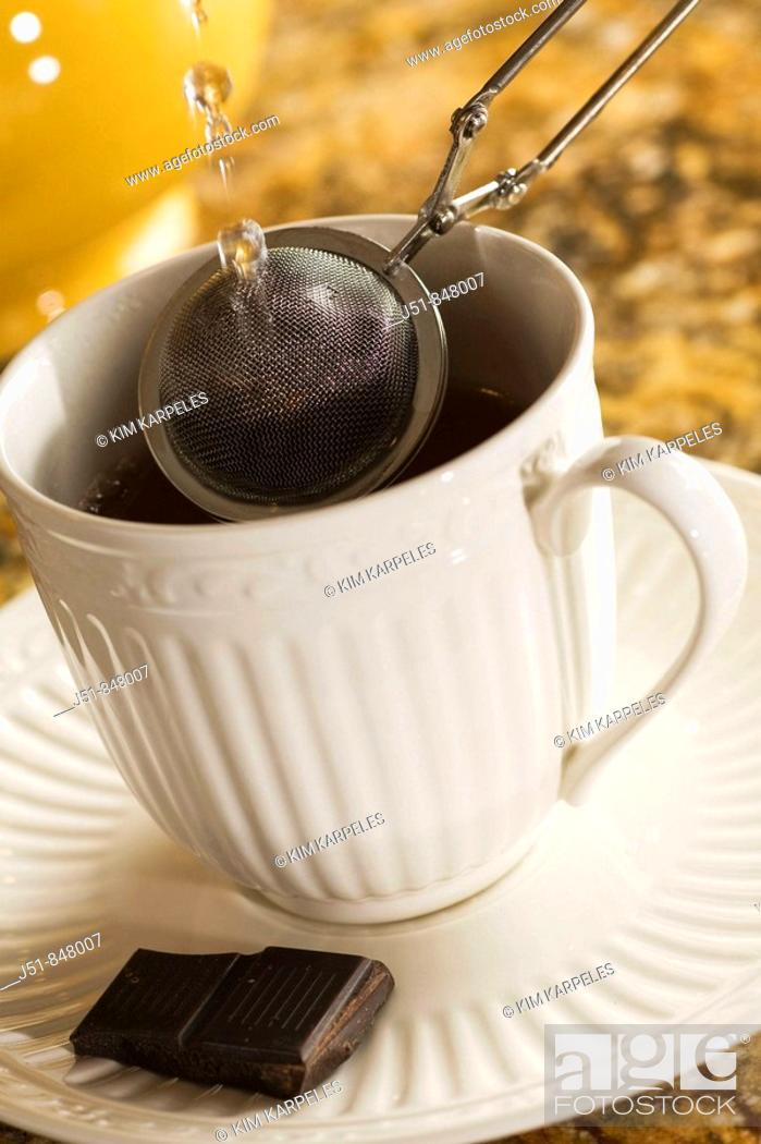 Stock Photo: STILL LIFE Pouring hot water through mesh strainer for loose leaf tea over cup and saucer, tea pot, piece of dark chocolate.