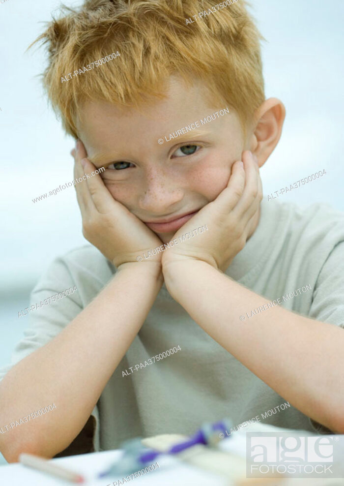 Stock Photo: Little boy holding head, smiling.
